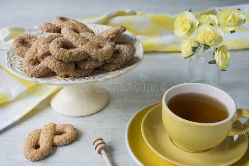 Le biscuit traditionnel des Pays-Bas a appel? Krakeling, sur le support de g?teau blanc Tasse jaune de th? photographie stock