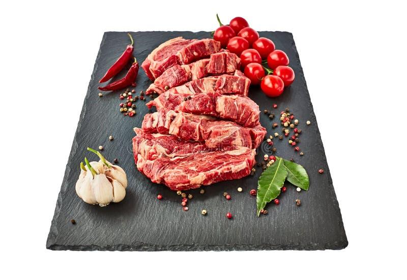 Le bistecche di manzo crude fresche con pepe ed i pomodori sull'ardesia nera imbarcano Isolato sopra fondo bianco Copi lo spazio immagini stock