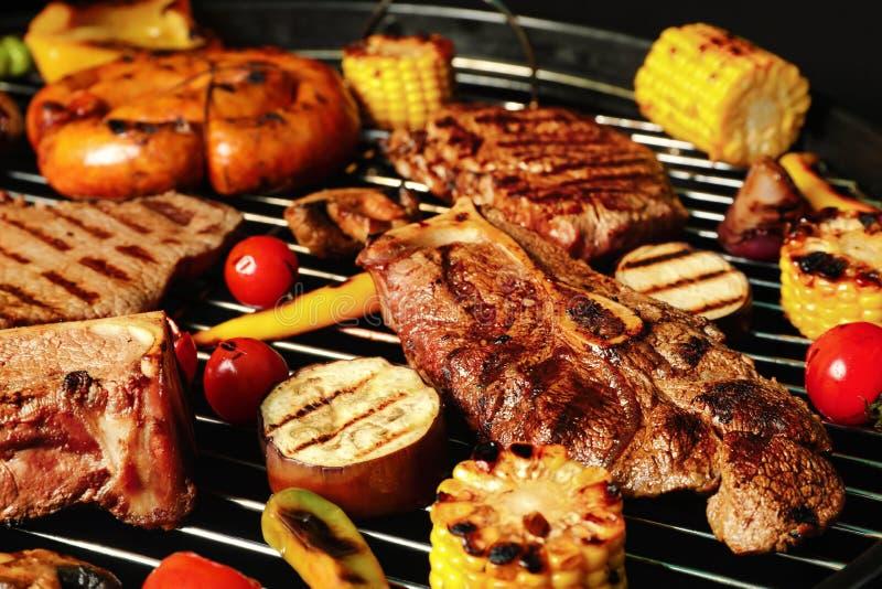 Le bistecche e le verdure arrostite fresche della carne sul barbecue grattano immagini stock libere da diritti