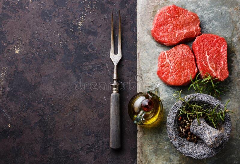 Le bistecche marmorizzate fresche crude della carne con i condimenti e la carne si biforcano fotografie stock libere da diritti