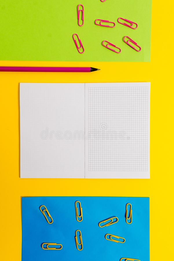 Le blanc a ajust? les feuilles de papier color?es de carnet que les agrafes crayonnent le fond de couleur de plaine de pointe de  photo libre de droits