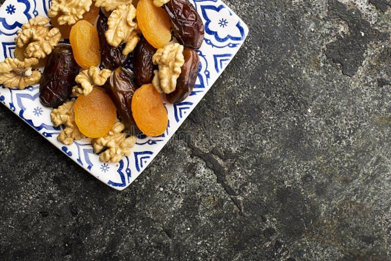 Le blanc bleu a peint le plat carré plein des noix et a séché des fruits : noix, pruneaux, dates, abricots secs sur un gris-foncé photo stock
