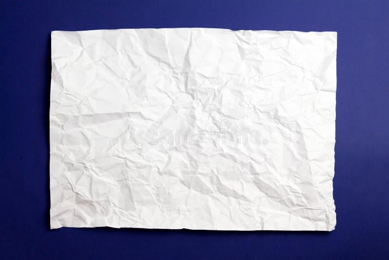 Le blanc a chiffonné la texture de papier sur le fond bleu images libres de droits
