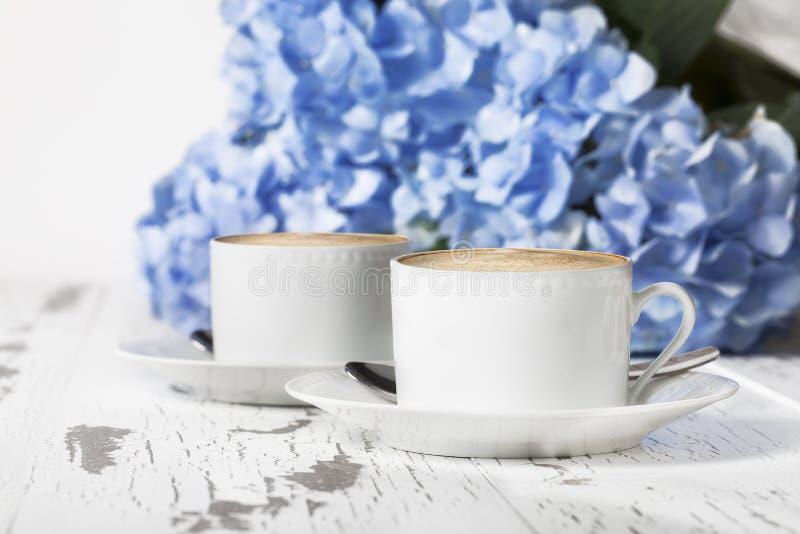 Le blanc d'expresso met en forme de tasse des hortensias images stock