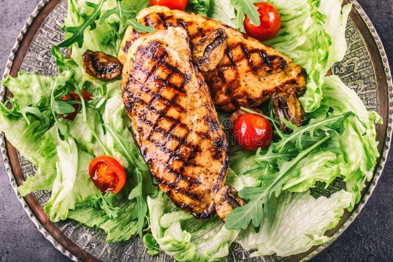 Le blanc de poulet grillé dans différentes variations par rapport aux herbes de champignons de tomates-cerises de salade de laitu photo libre de droits