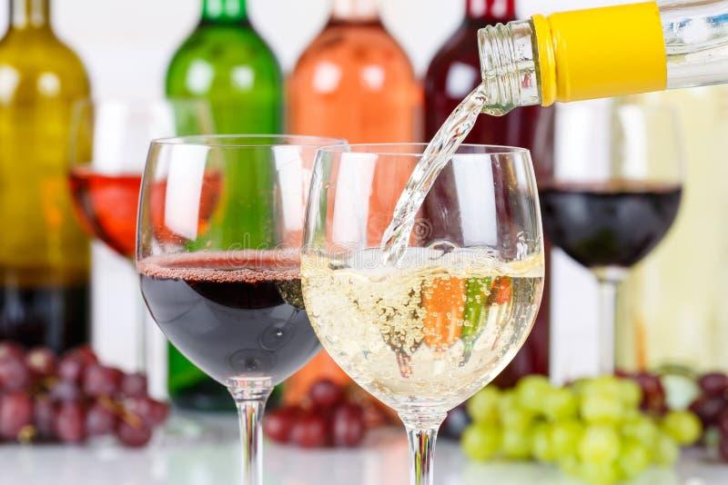 Le blanc de versement de bouteille en verre de vin versent photographie stock libre de droits