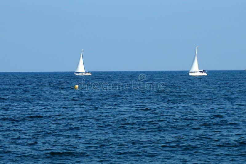 Le blanc embarque des voiliers ou des yachts flottant en mer photos stock