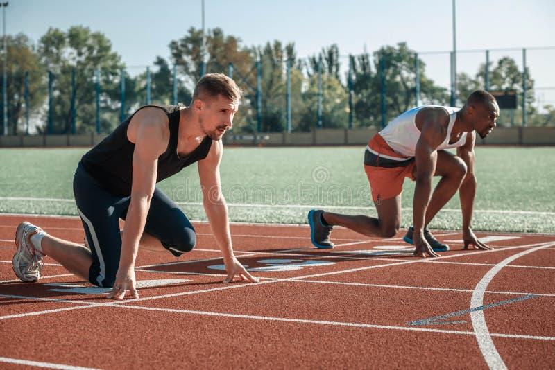 Le blanc et les athlètes d'hommes de couleur regardent à bon escient en avant photos libres de droits