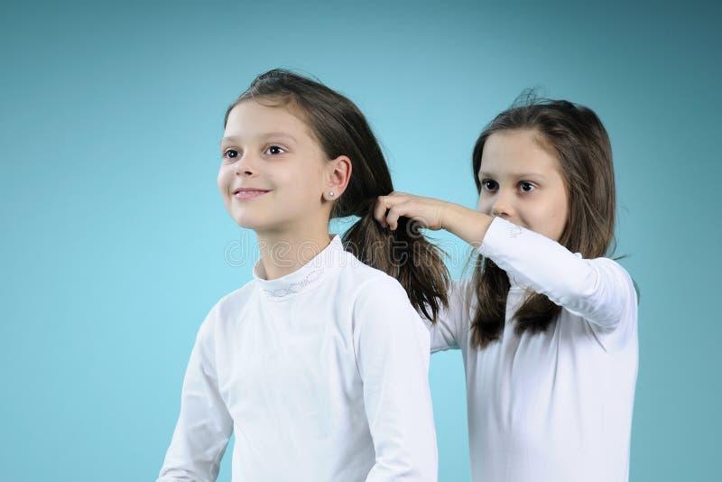 Le blanc jumelle des soeurs tissant le cheveu photographie stock