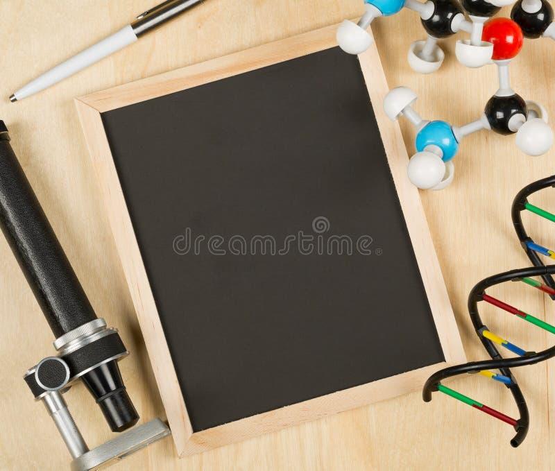 Le blanc, le tableau vide et noir avec le microscope, le modèle de molécule, le stylo et appartement du modèle d'ADN s'étendent s photo stock