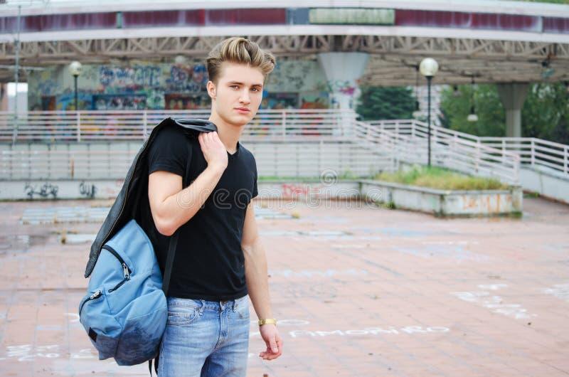 Le bleu attrayant a observé, jeune homme blond avec le sac à mêlée dehors photo stock