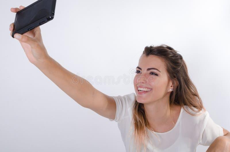 Le bleu de jeunes assez a observé la fille faisant un selfie images stock