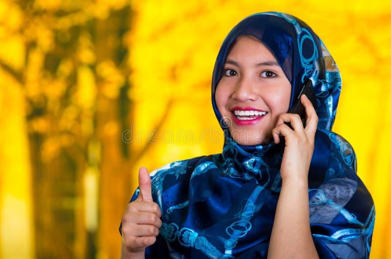 Le bleu de port de belle jeune femme musulmane a coloré le hijab, faisant face à l'appareil-photo posant renoncer heureusement au image stock