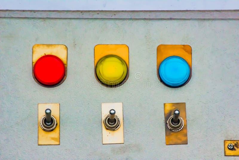 Le bleu jaune rouge allume l'indicateur avec le commutateur en métal de changement sur un panneau en acier de conseil photos libres de droits