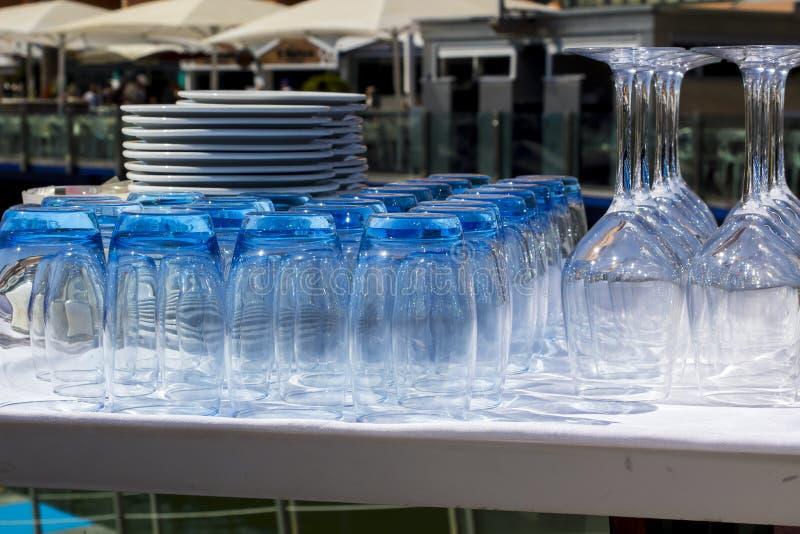 Le bleu a teinté des culbuteurs et des verres de vin avec des plats empilés dans un r images libres de droits