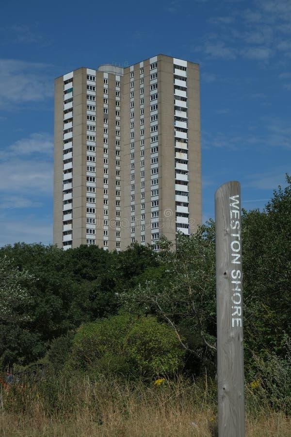 Le bloc de tour résidentiel monte hors des bois image stock