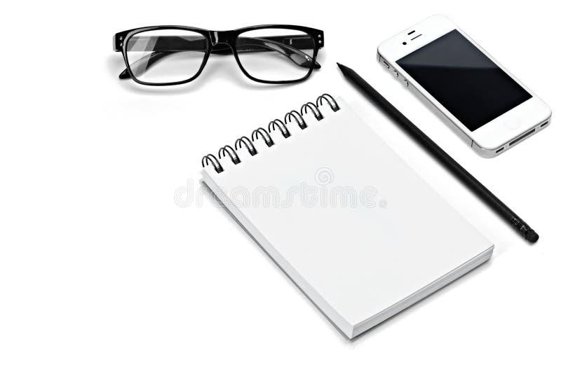 Le bloc-notes blanc de carnet de spirale vide de calibre, verres, crayon, smartphone a isolé le fond blanc photographie stock libre de droits