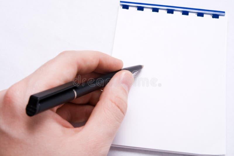 le bloc-notes blanc de message de main écrivent l'écriture photographie stock