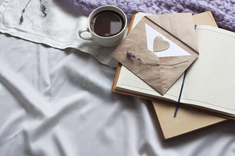 Le bloc-notes est une tasse de café et d'un livre avec la tonalité beige Tonalité de lavande d'écharpe de plaid de mode de vie de images stock