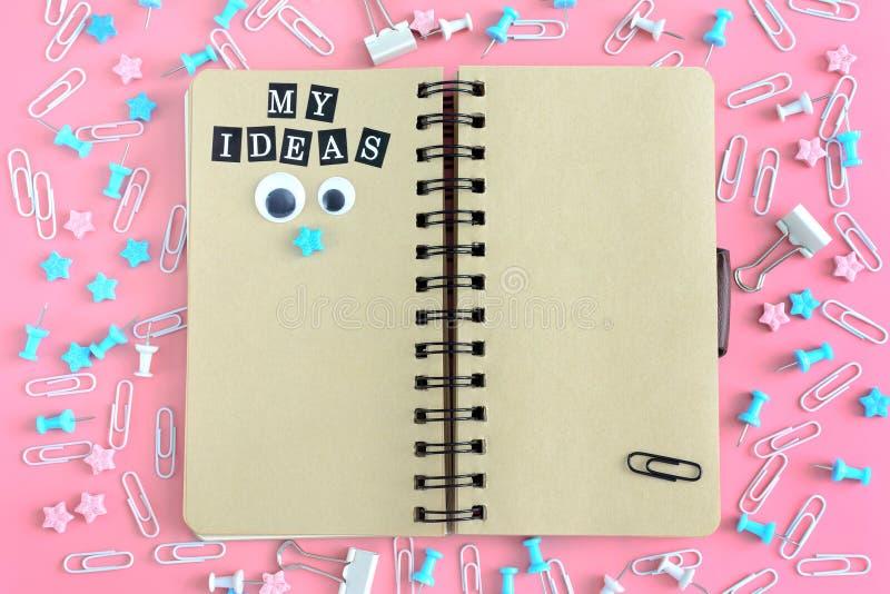 Le bloc-notes les ressorts est ouvert À côté de la papeterie Aux pages brunes du carnet il y a une inscription images libres de droits