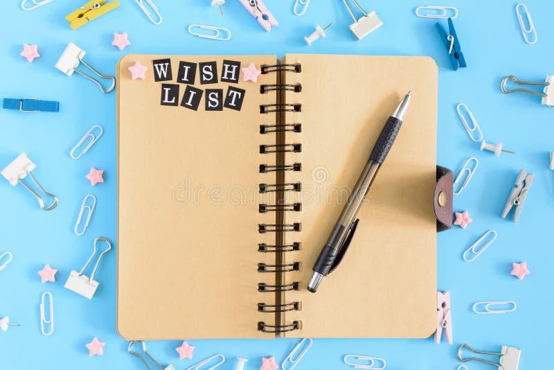Le bloc-notes les ressorts est ouvert À côté de la papeterie Les pages brunes du carnet ont le souhait d'inscription photos stock