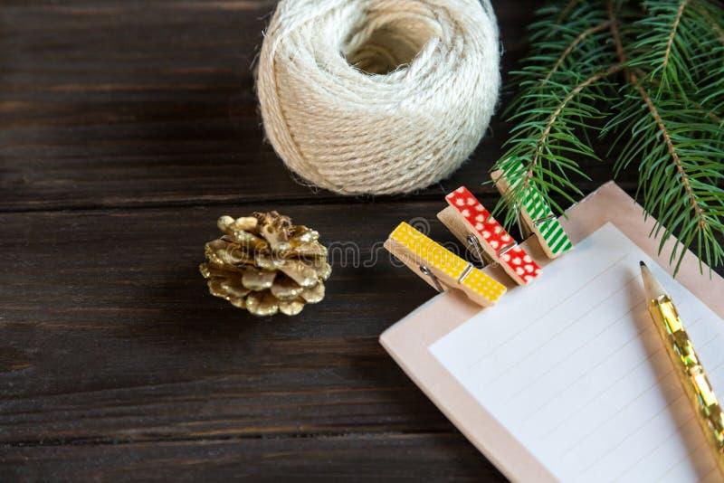 Le bloc-notes s'étend sur le fond en bois pour faire une liste pour faire des choses, la résolution ou la liste de présents pour  photo libre de droits