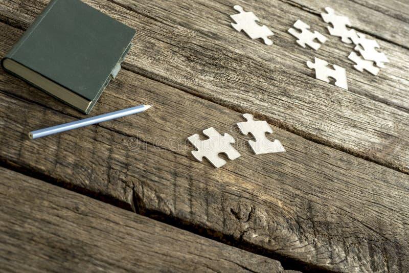 Le bloc-notes vert, le crayon et le puzzle dispersé rapièce le mensonge sur un te photographie stock