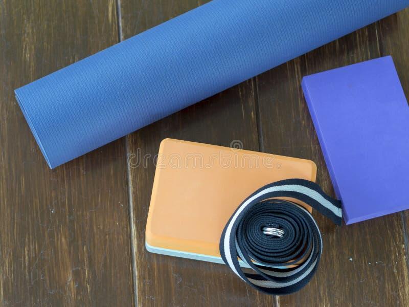 Le bloc réglé de yoga ceinture le tapis de courroie sur le bois images stock
