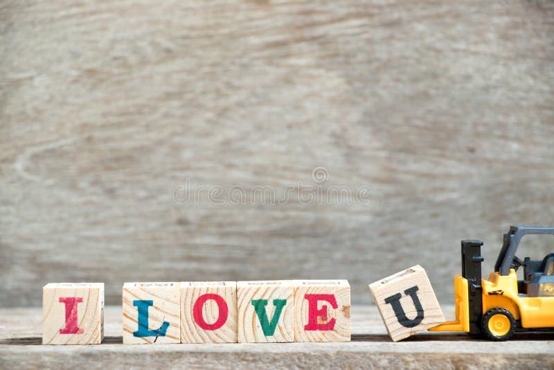 Le bloc u de lettre de prise de chariot élévateur de jouet pour accomplir le mot j'aime u sur le fond en bois et le x28 ; Concept photo libre de droits