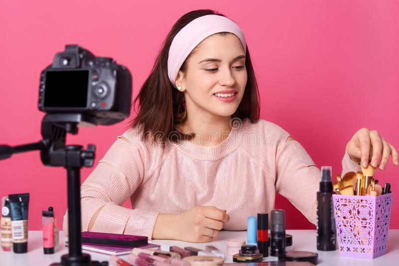 Le blogger féminin de charme montre des produits de cosmétiques tout en enregistrant la vidéo et donne des conseils pour son blog images libres de droits