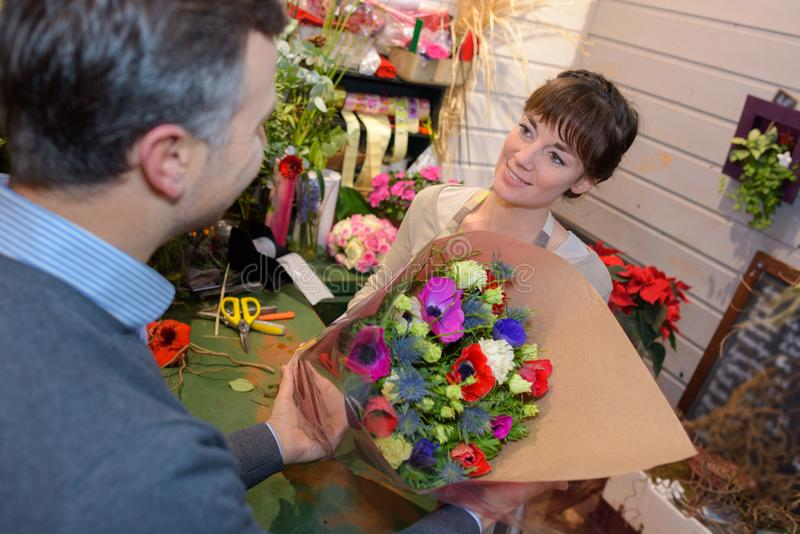 Le blomsterhandlaredanandebuketten för och mannen på blomsterhandeln arkivbild