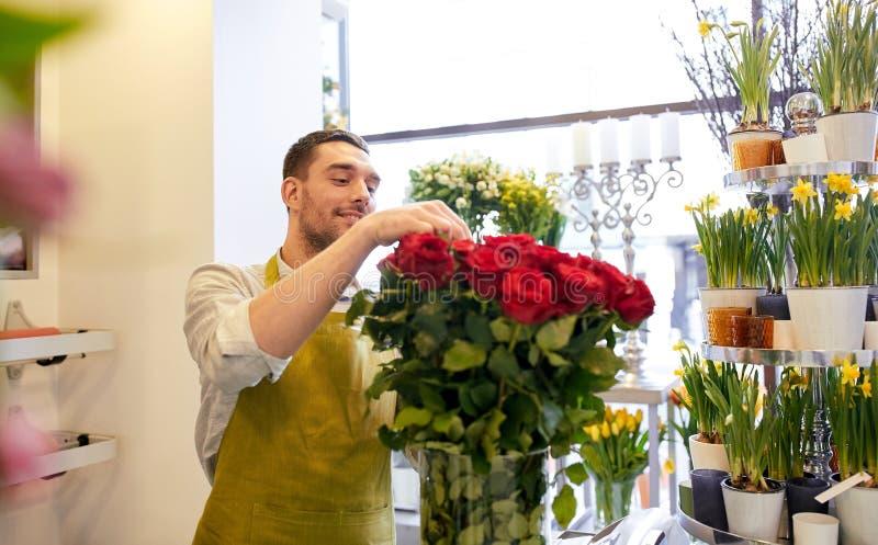 Le blomsterhandlaremannen med rosor på blomsterhandeln royaltyfria bilder