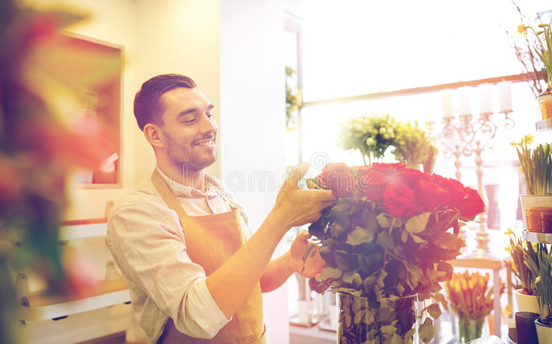 Le blomsterhandlaremannen med rosor på blomsterhandeln royaltyfri bild