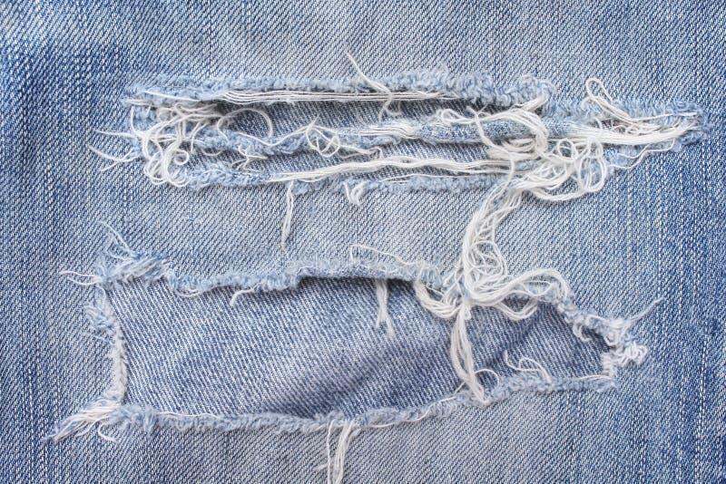 Le blue jeans di struttura con strappato su fondo, sul foro e sui fili bianchi hanno distrutto i modelli su denim fotografia stock