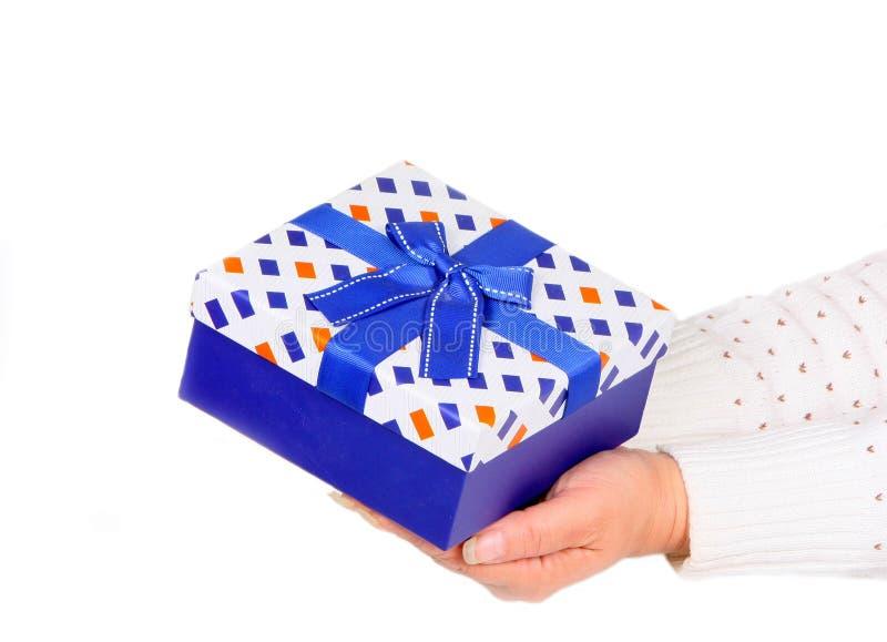 Le boîte-cadeau bleu chez des mains de la femme sur le blanc a isolé le fond Le concept de la surprise pour les vacances photographie stock