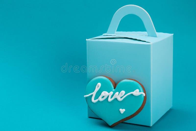 Le boîte-cadeau bleu sur un fond bleu, à côté de la boîte est un pain d'épice sous forme de coeur, le concept de l'amour et images libres de droits