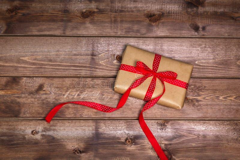 Le boîte-cadeau enveloppé de vintage avec l'arc rouge de ruban sur le fond en bois peut employer le Saint Valentin images stock