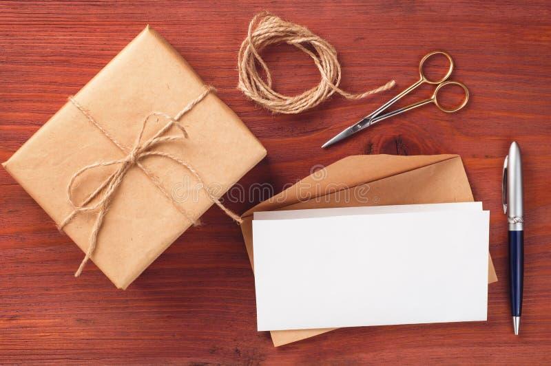 Le boîte-cadeau et l'enveloppe avec la feuille de papier blanc ont décoré des accessoires sur la table en bois photo libre de droits