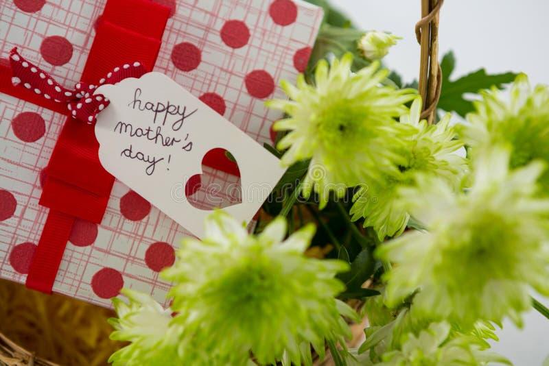 Le boîte-cadeau et le groupe de fleurs jaunes dans le panier en osier avec le jour de mères heureux étiquettent photographie stock