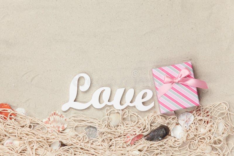 Le boîte-cadeau et le mot aiment avec le filet et les coquilles photographie stock libre de droits