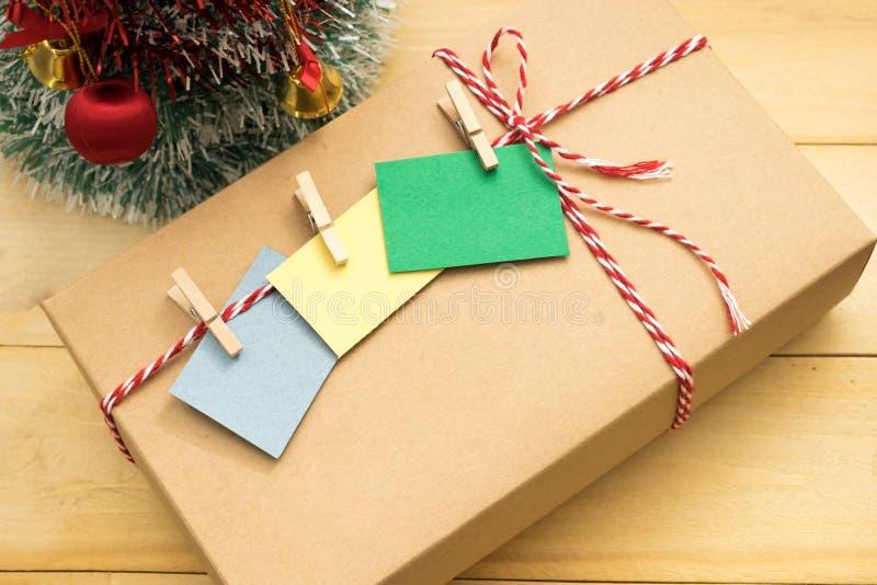 Le boîte-cadeau ont la note de post-it avec l'agrafe en bois sur la mise supérieure photographie stock libre de droits