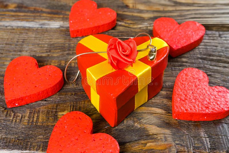 Le boîte-cadeau rouge sous la forme qu'il a formé la pantoufle en bois pendante avec le diamant, elle se tient sur un fond en boi photographie stock libre de droits