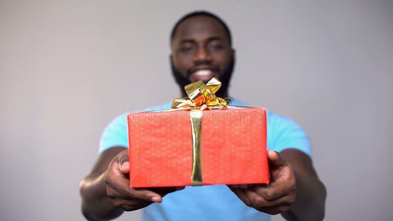 Le boîte-cadeau volontaire masculin noir de charité d'apparence à la caméra, présentent pour de pauvres enfants image stock