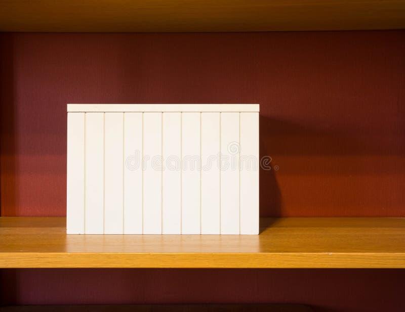 Le boîtier blanc sur en bois rayonnent image libre de droits