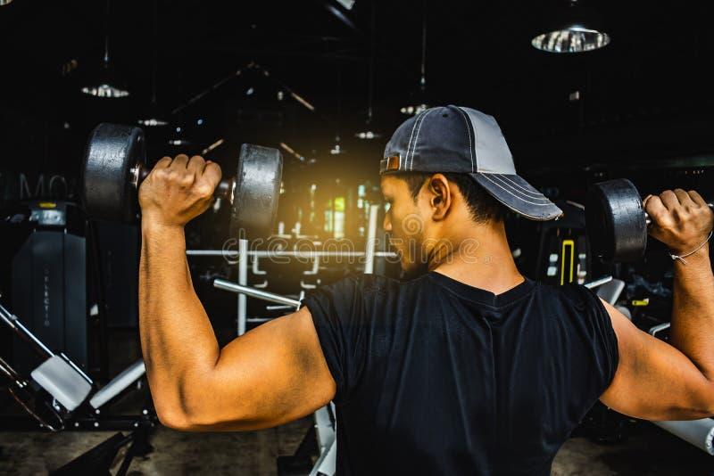 Le Bodybuilder asiatique d'homme avec l'haltère pèse l'athle bel de puissance photographie stock libre de droits