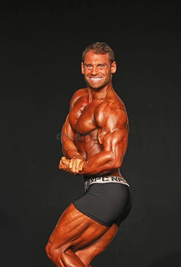 Le Bodybuilder beau et Hunky éclate la pose de Côté-coffre photo stock