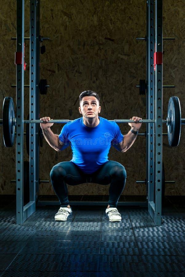 Le bodybuilder d'athlète dispose à soulever une barre lourde image libre de droits