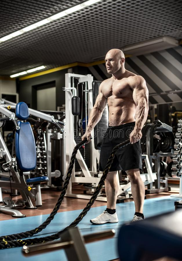 Le bodybuilder d'homme exécutent l'exercice image stock