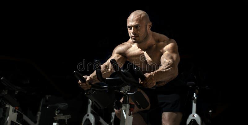 Le bodybuilder d'homme exécutent l'exercice photographie stock