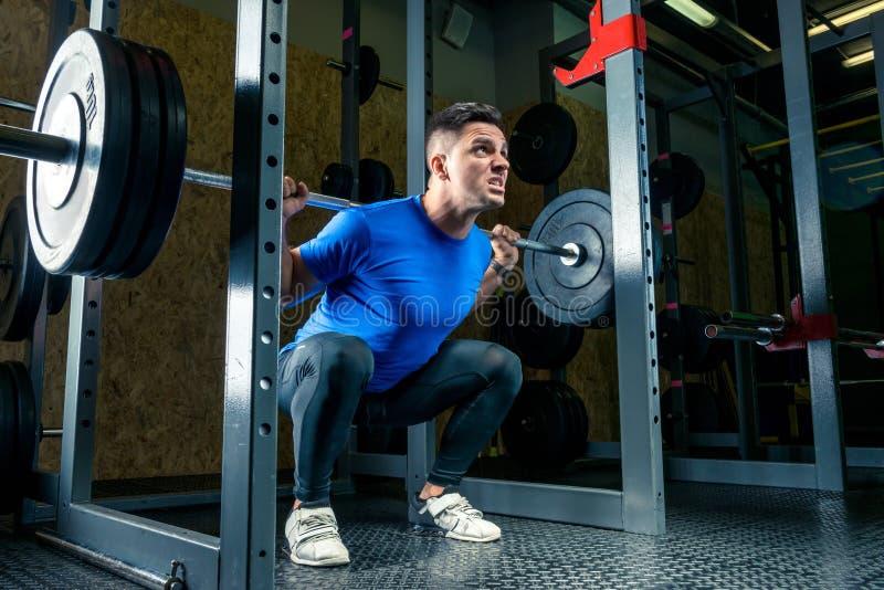 Le Bodybuilder dans un T-shirt bleu soulève une barre pesant 60 kilogrammes dans photo libre de droits